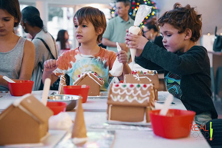 Kids enjoying the Gingerbread House Decorating class at The Real Food Academy
